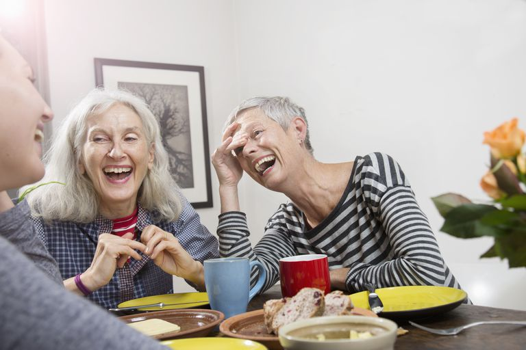 Women laughing, having lunch at home.