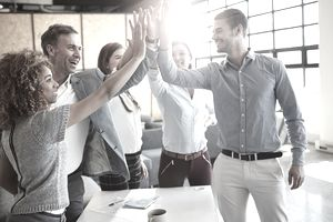 High five! Business people working together as a team in an office.
