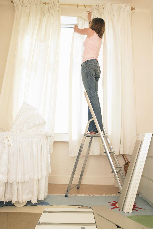 Woman hanging curtains on her nursery windows