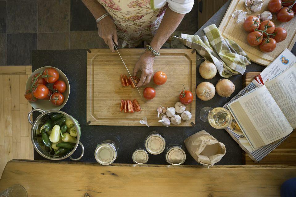 Overhead view woman cutting tomatoes on cutting board