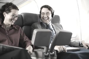 Laughing passengers watching movie on airplane