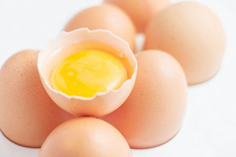 Close-Up Of Egg Carton With Broken Egg