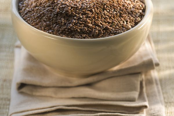 Bowl of flax seeds on napkin, close-up