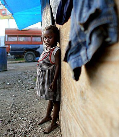 An orphan stands by a Haiti orphanage, which is currently housed in tents in a tent city in Haiti.