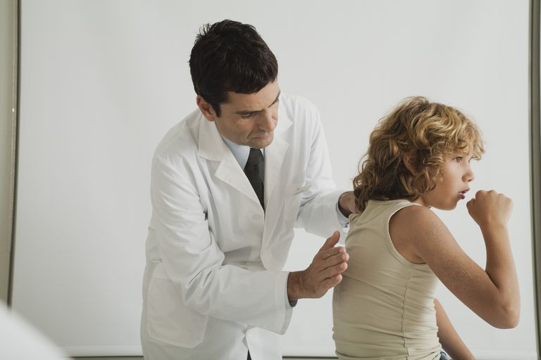 Doctor checking young patient's cough