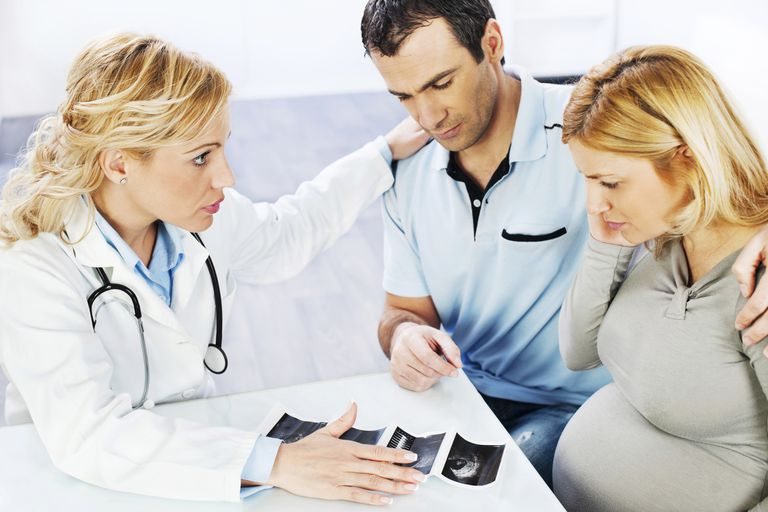 pregnant couple talking to doctor