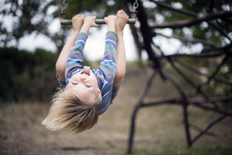 Joyful boy playing on playground swing