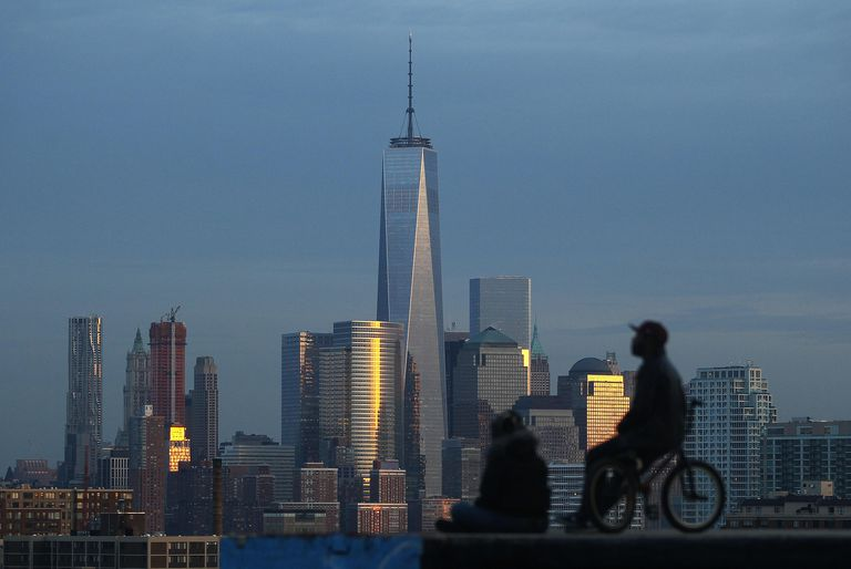 Two people look out at Lower Manhattan and One World Trade Center in New York from a park in New Jersey
