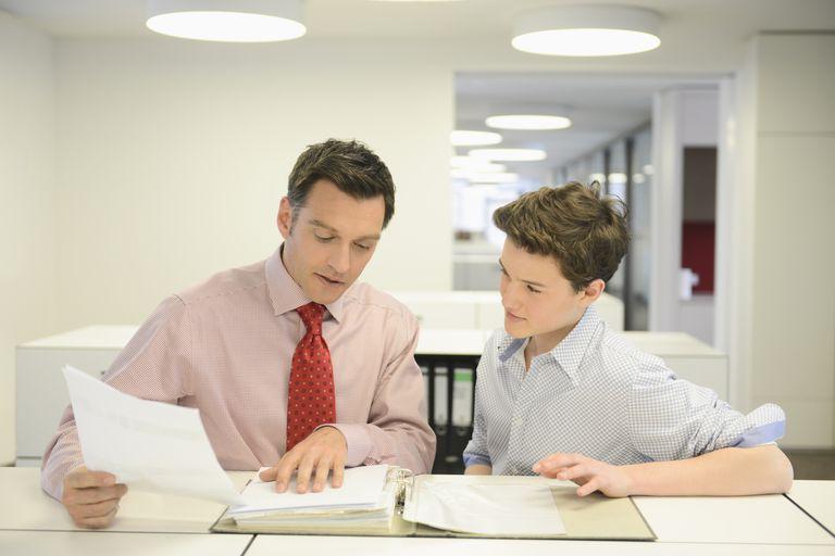 Boy learning from businessman at internship