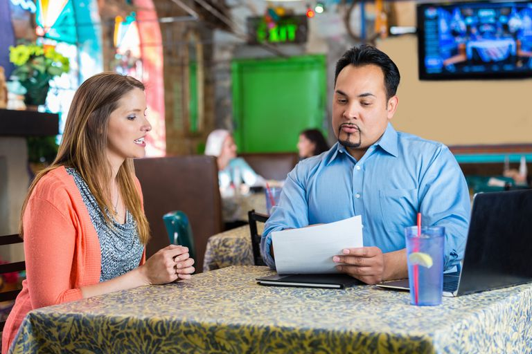 Restaurant manager reading resume and interviewing young woman for job