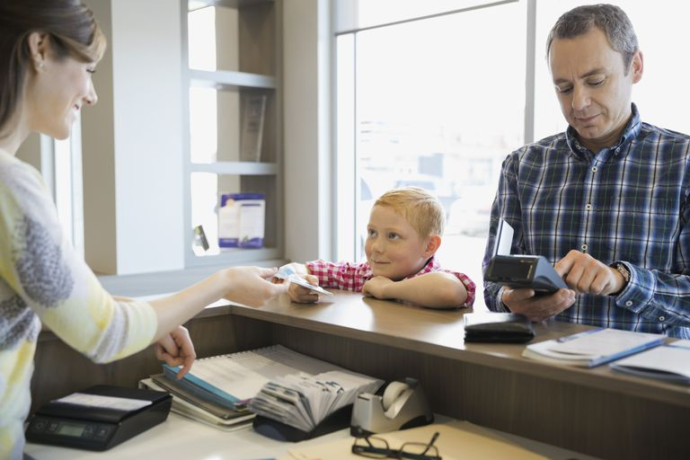 Receptionist helping father and son in dentists office