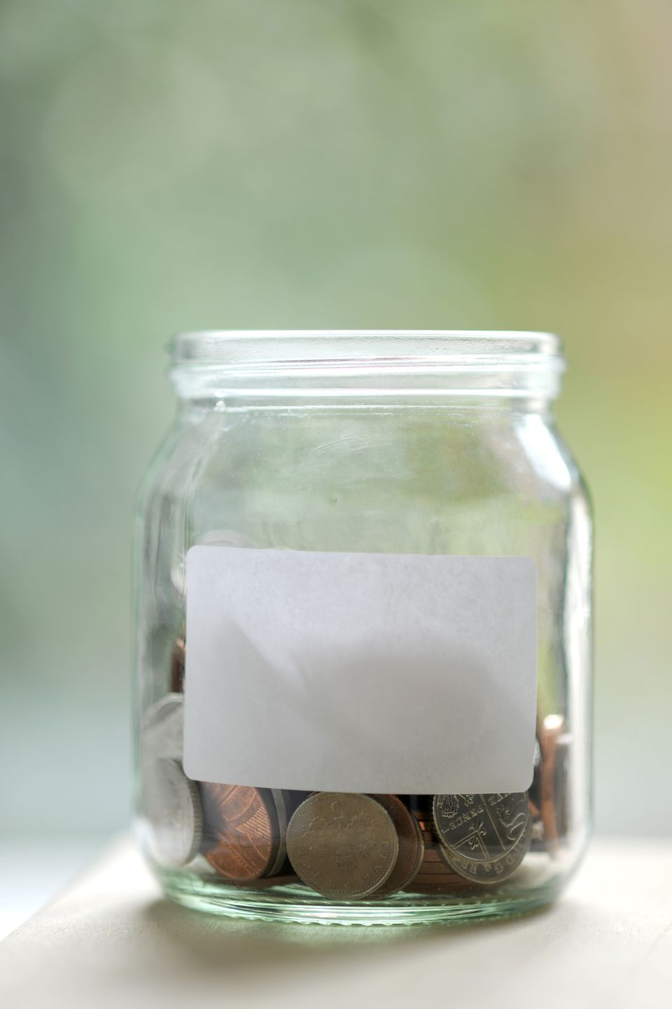 Jam jar filled with coins and blank label
