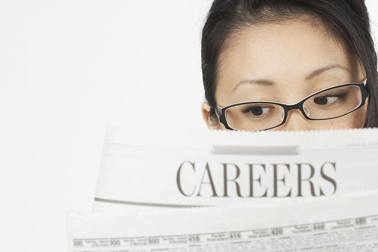 An Asian American woman looks at job listings in a newspaper. A new study found that working below one's skill level can harm future hiring outcomes.