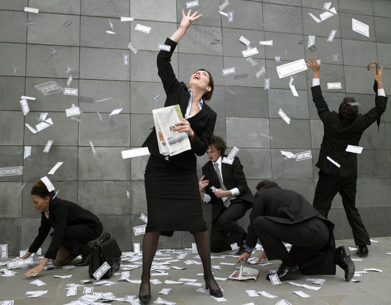 People in suits throw money into the air and gather it from the ground