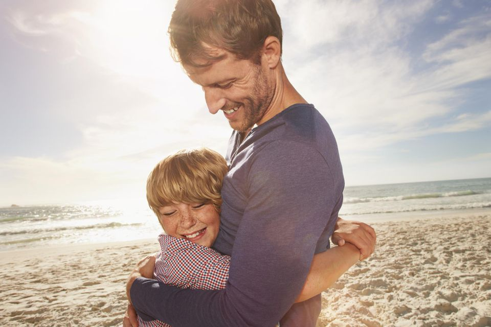Father and son (6-8) hugging outdoors