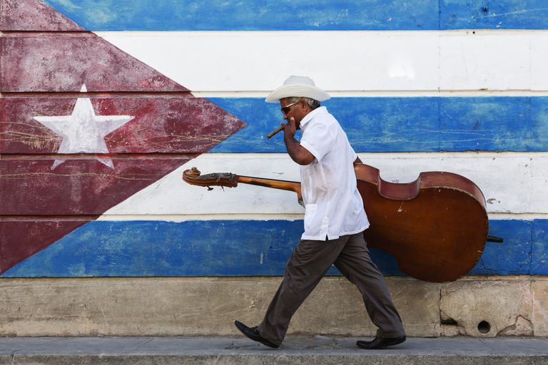 Hispanic musician carrying upright bass in front of Cuban flag mural
