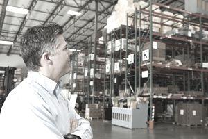 USA, California, Santa Ana, Businessman looking at goods in warehouse