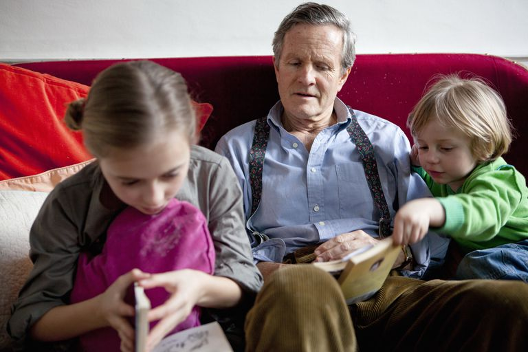 Grandfather reading books with children