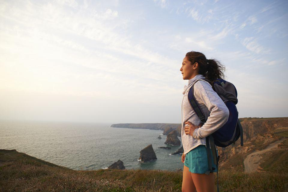 Profile of female hiker on Atlantic coastline.