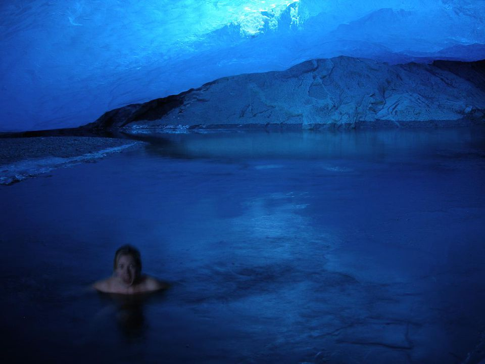 Winter/ice swimming in the glacier pond in the glacier cave underneath the Nigardsbreen, Jostedalsbreen Simone Stibbe swimming in glacial cave lake.