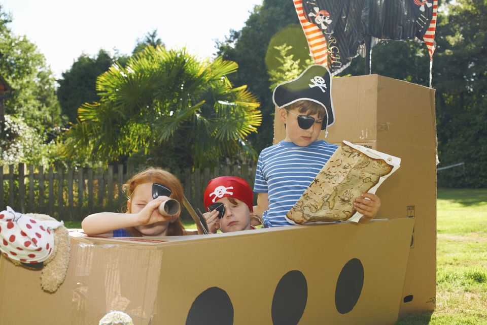 A picture of kids playing in a cardboard pirate ship