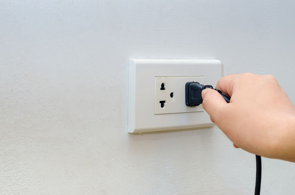 hand outlet Power saving Hand inserting electrical plug into outlet