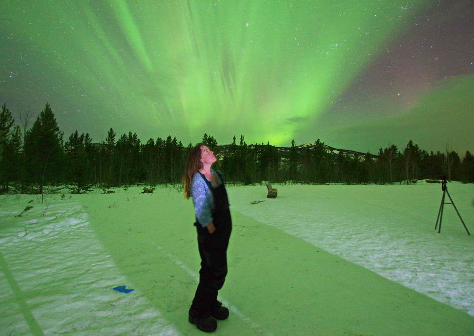 a woman standing in the snow under a northern lights display