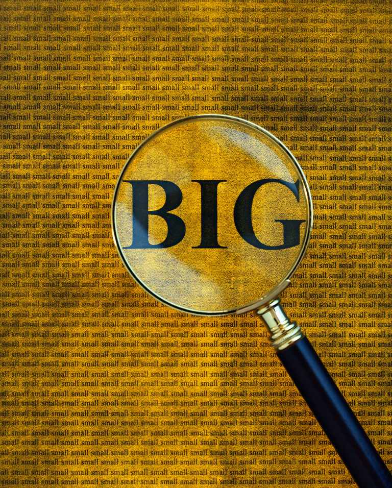 Magnifying glass showing word 'BIG' among lines of small text
