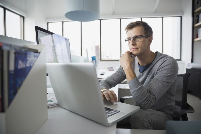 Focused architect working at laptop in office