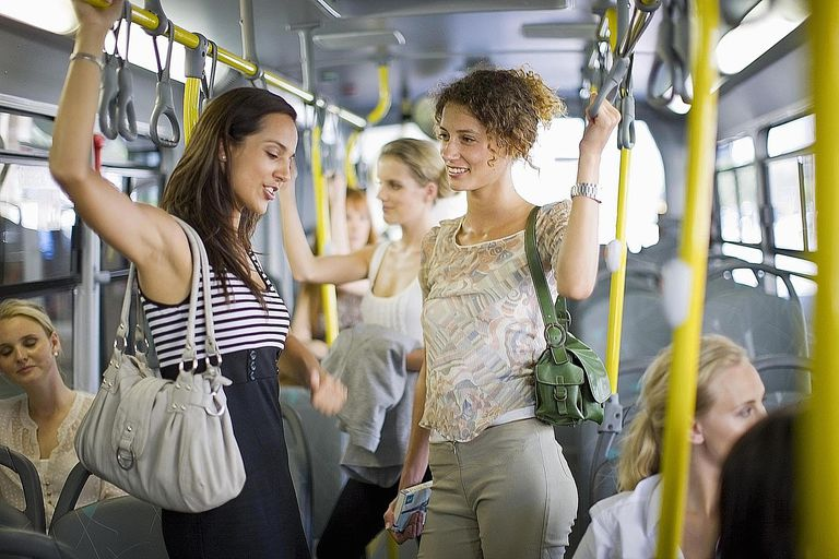 Women stand and hold the hand rails on a public bus. Participant observation often involves studying how people interact in public spaces like these.