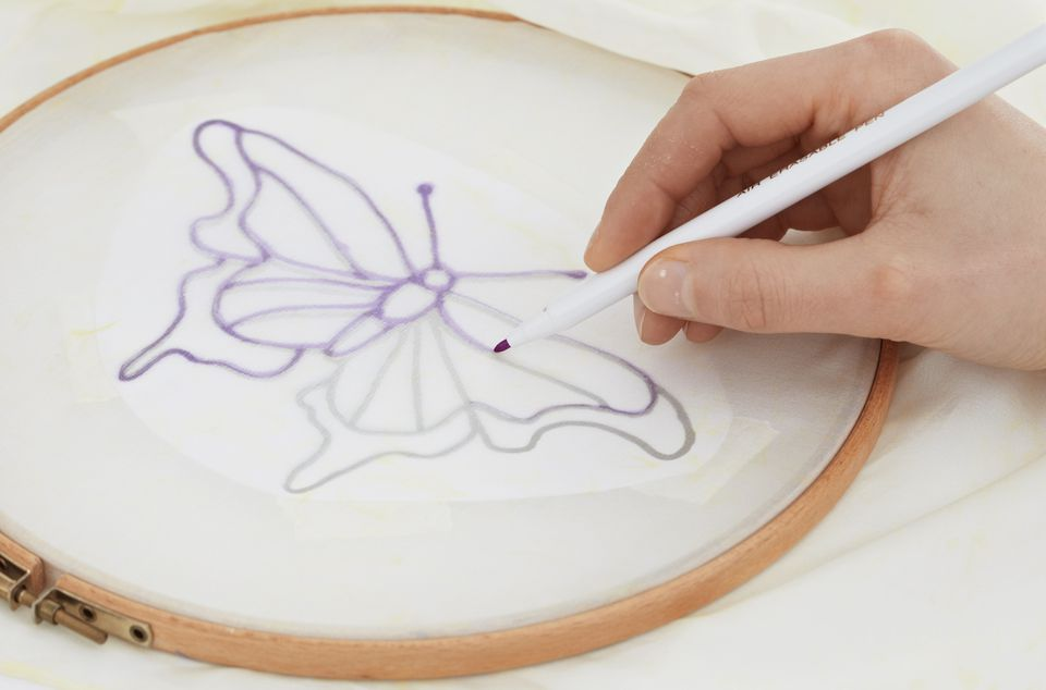 Tracing over lines of butterfly motif on silk scarf secured to embroidery hoop, close-up