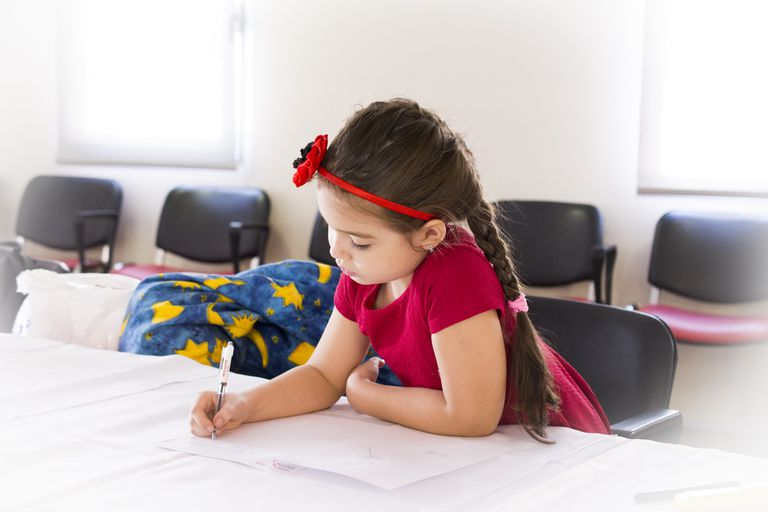 young girl writing in a classroom