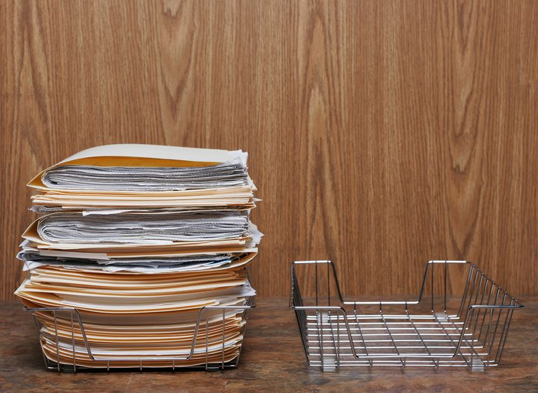 A pile of folders in wire basket next to empty basket.