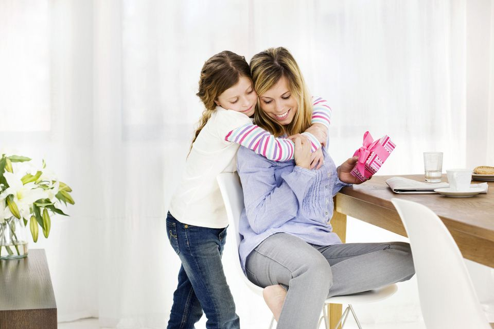 A picture of a mom hugging her child for a present