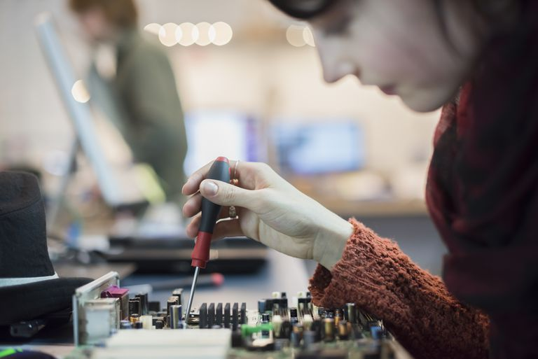 Computer Repair Shop. A woman using an electronic screwdriver tool on a computer circuit board.
