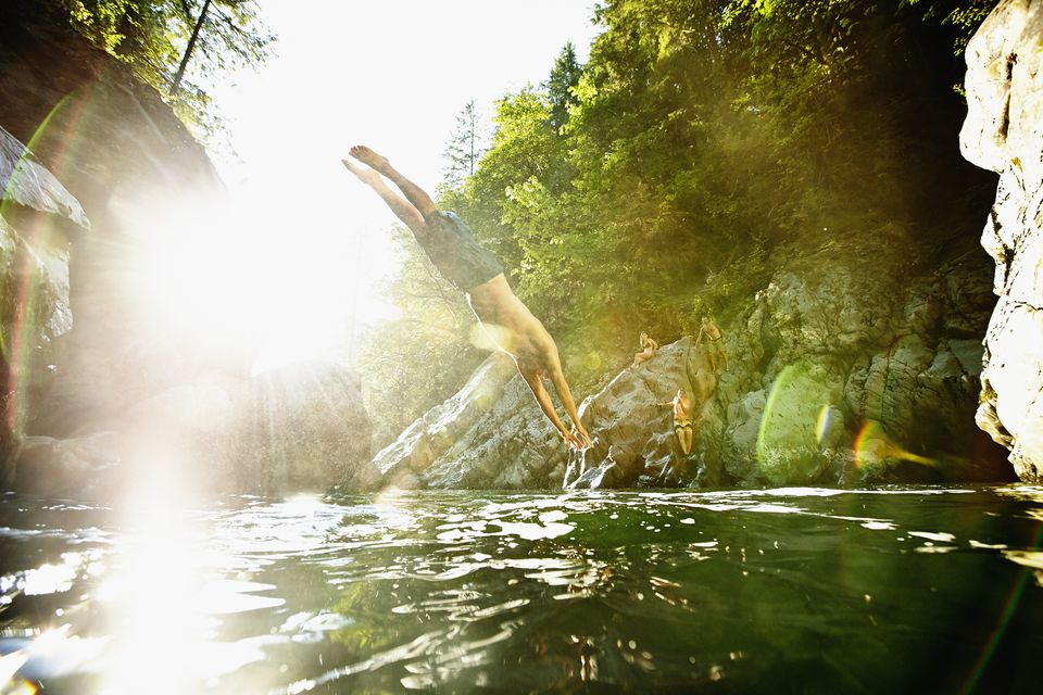 Man diving off of rock into swimming hole with friends nearby.