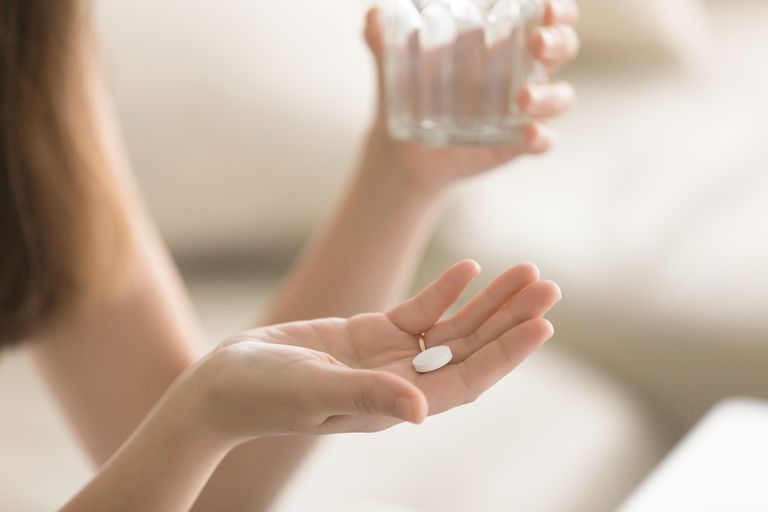 Close up photo of round white pill in female hand