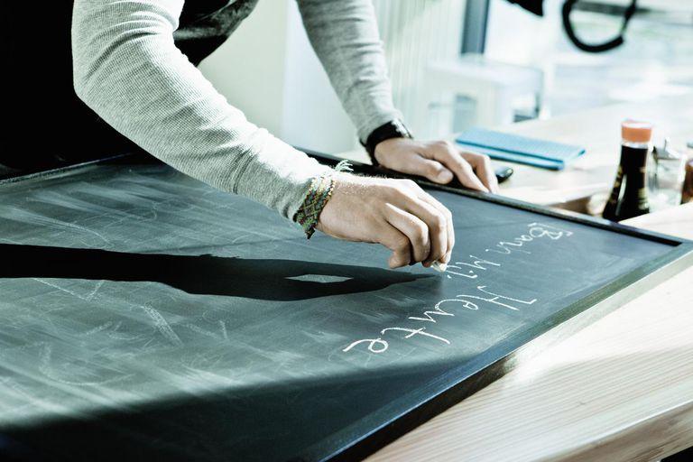 Worker writing on restaurant chalkboard