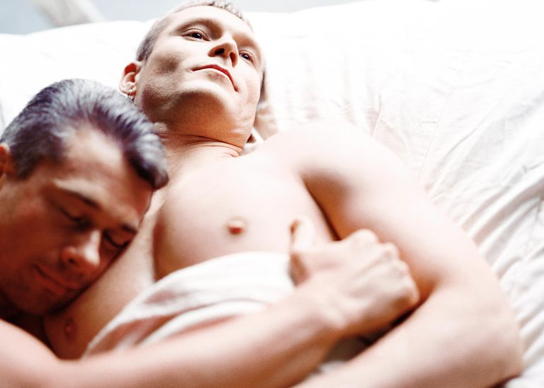 A gay couple lying in bed together