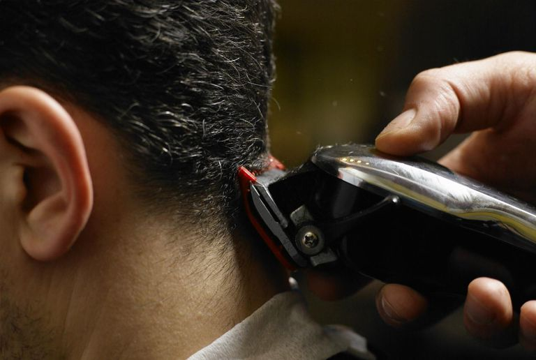 Barber cutting man's hair, close-up of electric razor