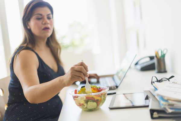 USA, New Jersey, Jersey City, Woman eating salad and using laptop in office