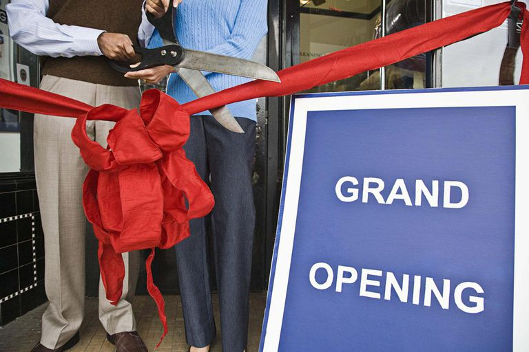 People cutting ribbon at grand opening of store
