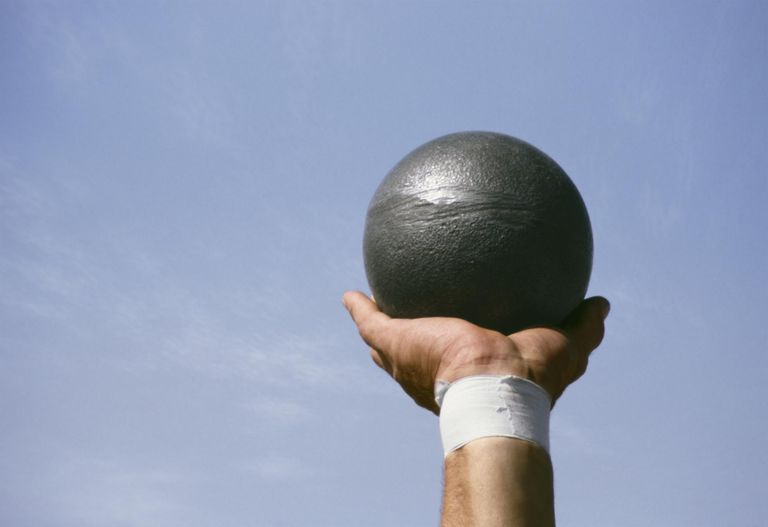 Athlete holding shot put, only arm visible