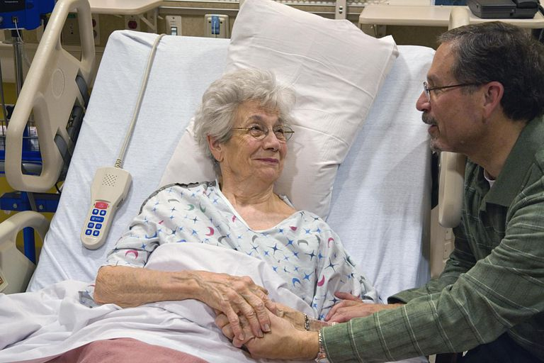 Son visiting senior mother in hospital, both holding hands