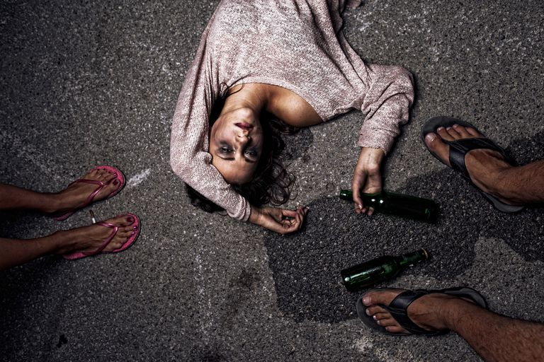 Drunk young woman lying on the street