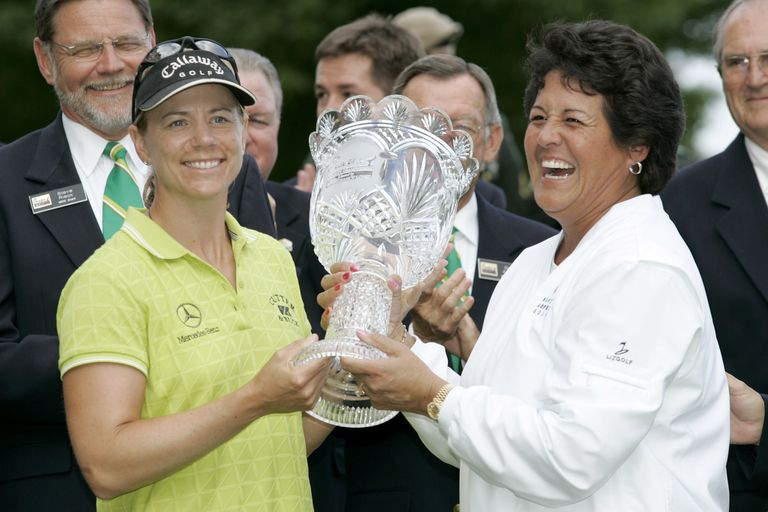 Tournament host Nancy Lopez presents Annika Sorenstam her trophy after winning the Chick-fil-A Charity Championship in 2005