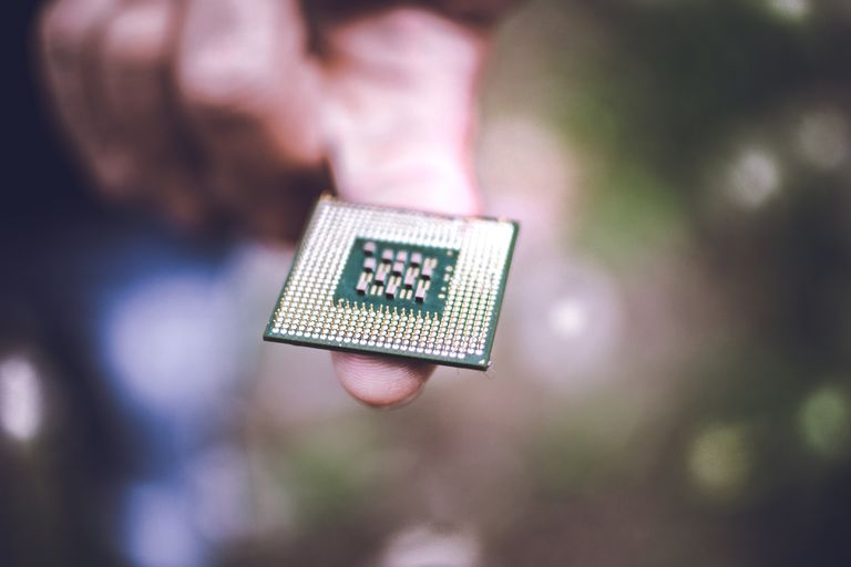 A computer processor balancing on a finger.