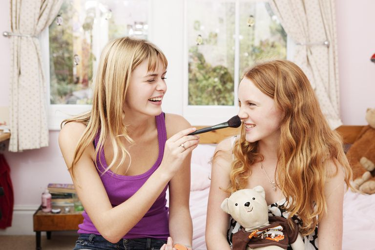 Girl tickling nose of sister with make-up brush