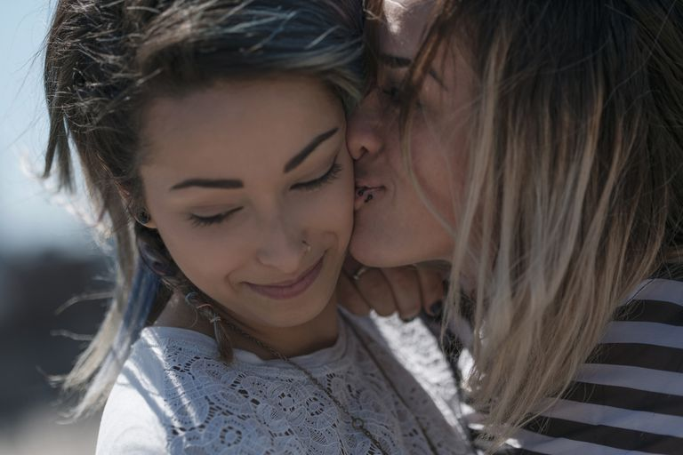 Young woman kissing partner on cheek