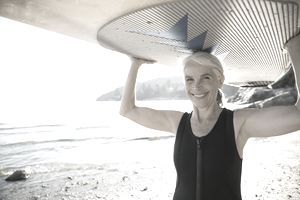 Senior woman holding paddle board overhead on beach
